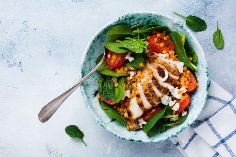 Салат с красными чечевицами, листьями шпината, томатами вишни, мясом цыпленка и сыром моццареллы с оливковым маслом в керамическо стоковые изображения rf