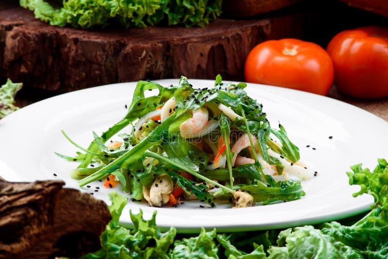 Салат с креветками, мидиями, кальмарами, салатом, arugula, шпинатом и другими зелеными цветами на белой плите на темной деревянно стоковые фотографии rf