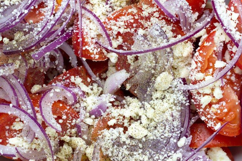 Салат с свежими томатами, красным луком и заскрежетанным сыром фета стоковая фотография