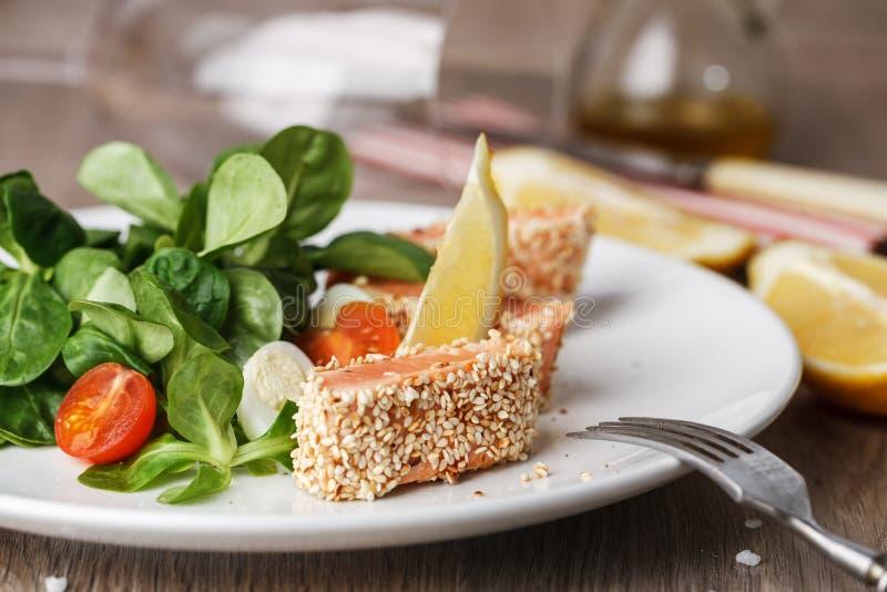 Салат с семгами зажарил в семенах сезама, томатах вишни и яичке триперсток на деревянном столе стоковое изображение rf