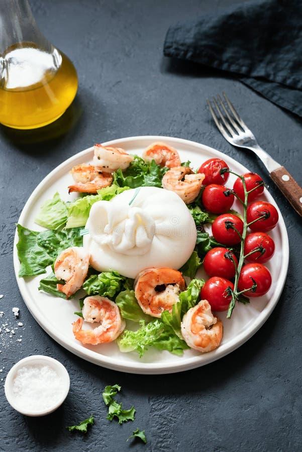 Салат с сыром, креветками, салатом и томатами burrata на белой плите стоковое изображение rf