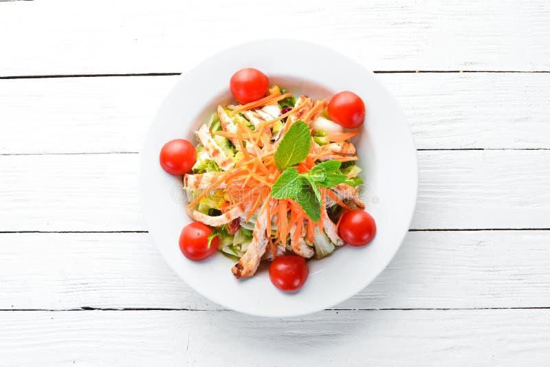 Салат с цыпленком и свежими овощами на белой предпосылке деревянной r стоковое фото
