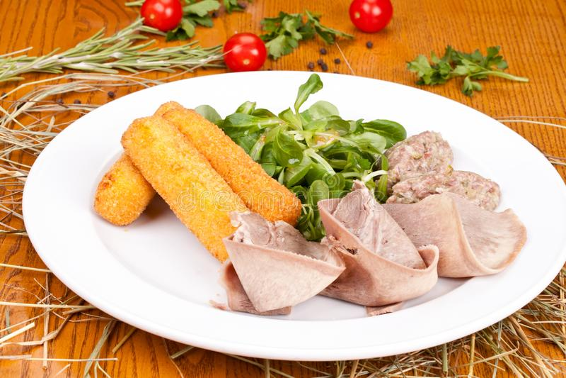 Салат с языком говядины, тартаром из говядины, ручками сыра и салатом lamb's на белой плите стоковые изображения