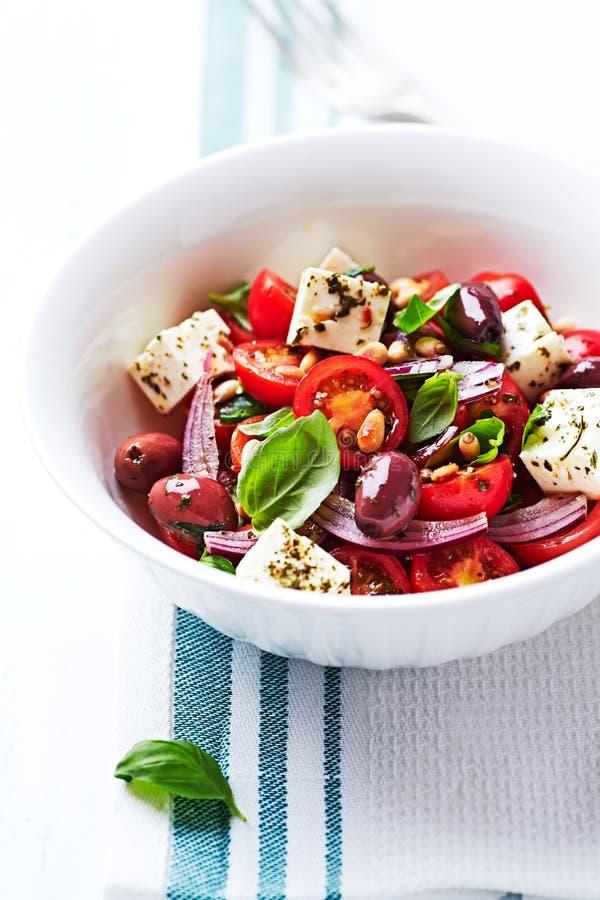 салат томата вишни Среднеземноморск-стиля с оливками Kalamata, сыром фета и гайками сосны стоковые фото