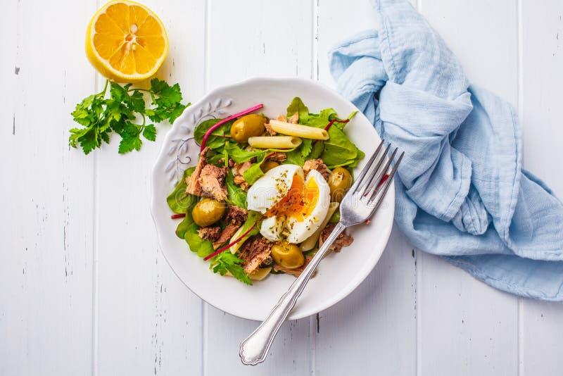 Салат тунца с макаронными изделиями, оливками и краденным яйцом в белой плите дальше стоковая фотография
