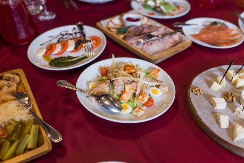 Салат цезаря с гренками, яичками триперсток, томатами вишни и зажаренным цыпленком в плите на таблице стоковая фотография