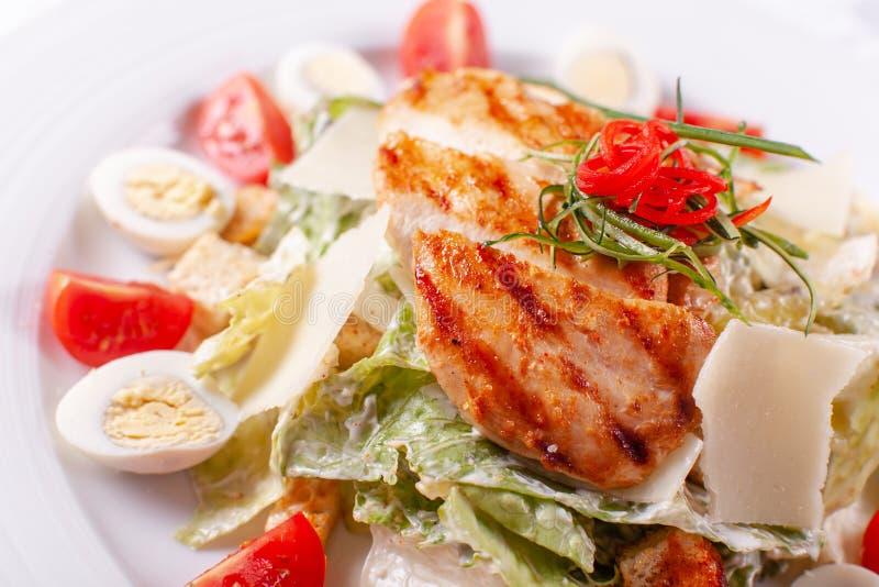 Салат цезаря с яичками триперсток, томатами вишни, сыр пармесаном и зажаренным цыпленком в белой плите на светлой таблице стоковые фотографии rf