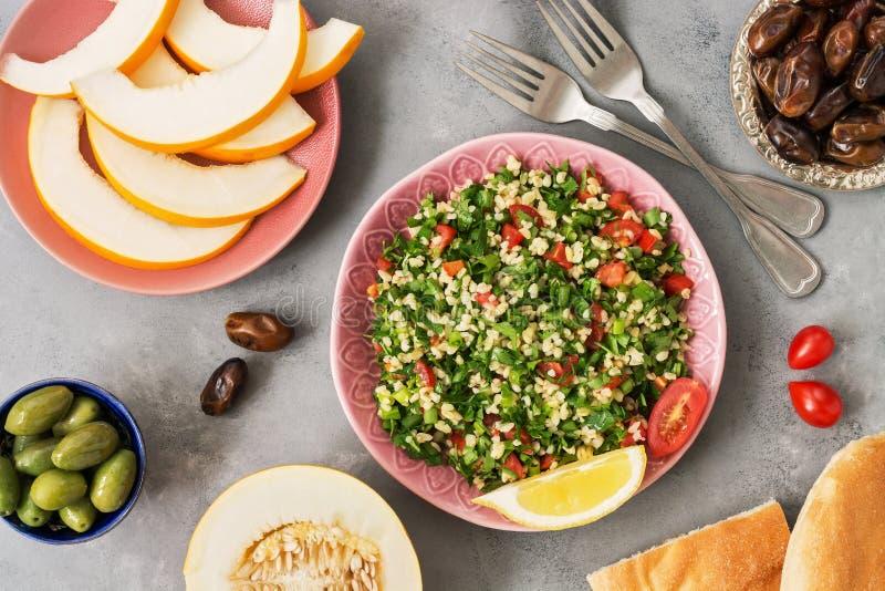 Салат Tabbouleh и различная ближневосточная или арабская еда, дыня, персик, дата, оливки на серой предпосылке Традиционная ливанс стоковая фотография rf