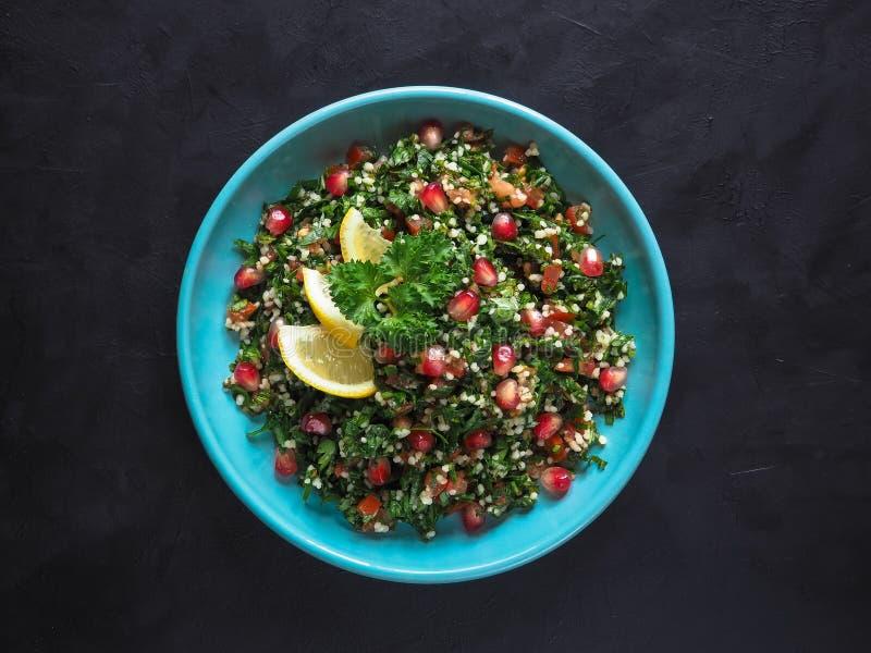 Салат Tabbouleh с кускус в шаре на черной таблице Салат Levantine вегетарианский с петрушкой, мятой, булгуром, томатом стоковое изображение