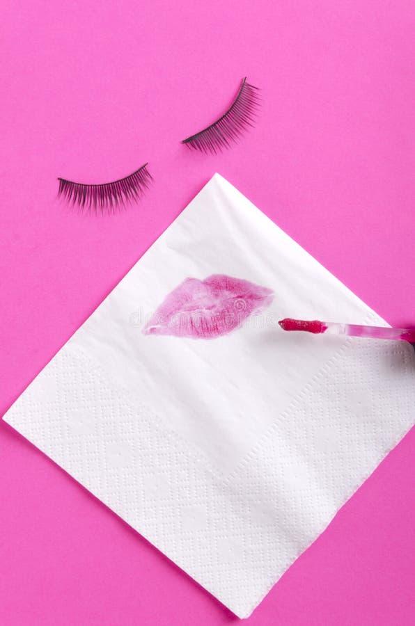 Салфетка и губная помада белой бумаги целуют на ей, ресницах faslse на розовой предпосылке Абстрактная концепция красоты женщины стоковые фото