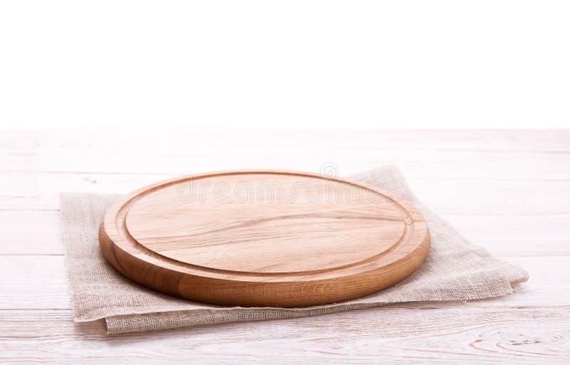 Салфетка и доска для пиццы на деревянном столе Холст, полотенца блюда на белой насмешке взгляд сверху предпосылки деревянного сто стоковые изображения