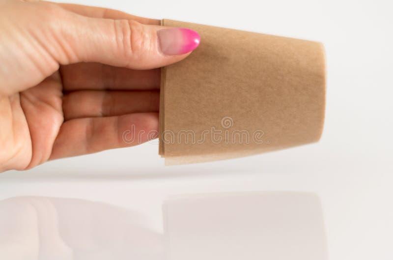 Салфетки рогожки косметические для того чтобы извлечь мазеподобный лоск от стороны в woman& x27; рука s стоковое фото rf