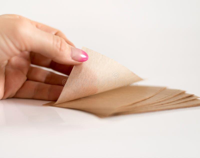 Салфетки рогожки косметические для того чтобы извлечь мазеподобный лоск от стороны в руке стоковое изображение