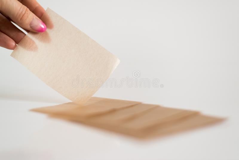 Салфетки рогожки косметические для того чтобы извлечь мазеподобный лоск от стороны в woman& x27; рука s стоковые фото