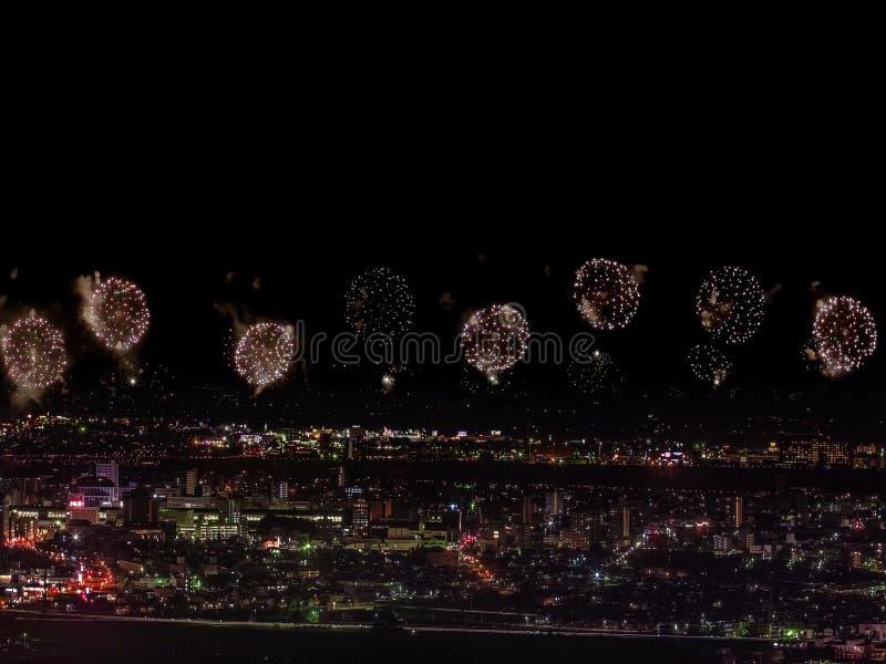 Салют над городом мегаполис Праздничный салют в ночном небе Взрывы фейерверков стоковые изображения