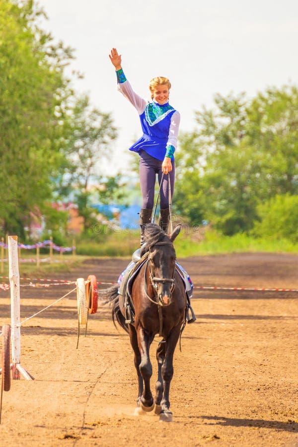 Самара, август 2018: казацкая девушка едет лошадь и выполняет фокусы стоковое изображение