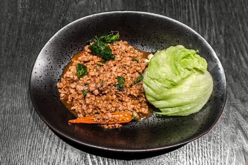 Самая лучшая Тайская кухня Stir зажарила свинину с листьями базилика добавляет свежий chili и свежие овощи в черной плите на дере стоковые фотографии rf