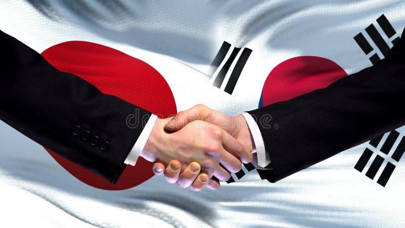Саммит приятельства рукопожатия Японии и Южной Кореи международный, предпосылка флага стоковые изображения rf