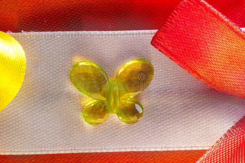 Самодельный элемент needlework оборачивать подарка, желтая бабочки сделанной из стекла и смычков лент сделанных красочного стоковое изображение