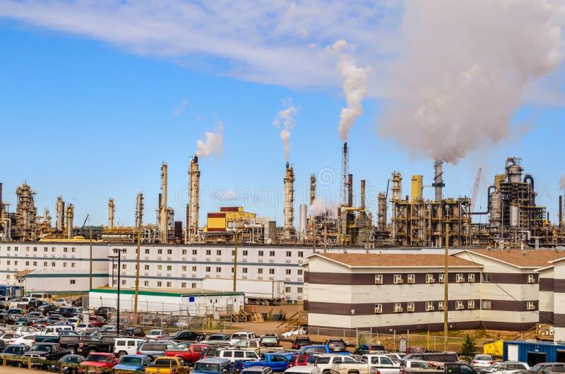 Самое большое канадское нефтеперерабатывающее предприятие на заднем плане, паркующ на переднем плане, куря трубы стоковое изображение