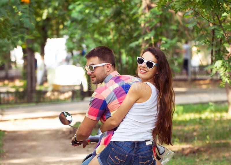 самокат riding совместно Молодые пары ехать самокат стоковая фотография rf