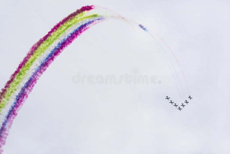 Самолеты на airshow с красочными пестроткаными следами дыма против голубого неба Воздушные судн, дисплей летая и стоковые изображения rf
