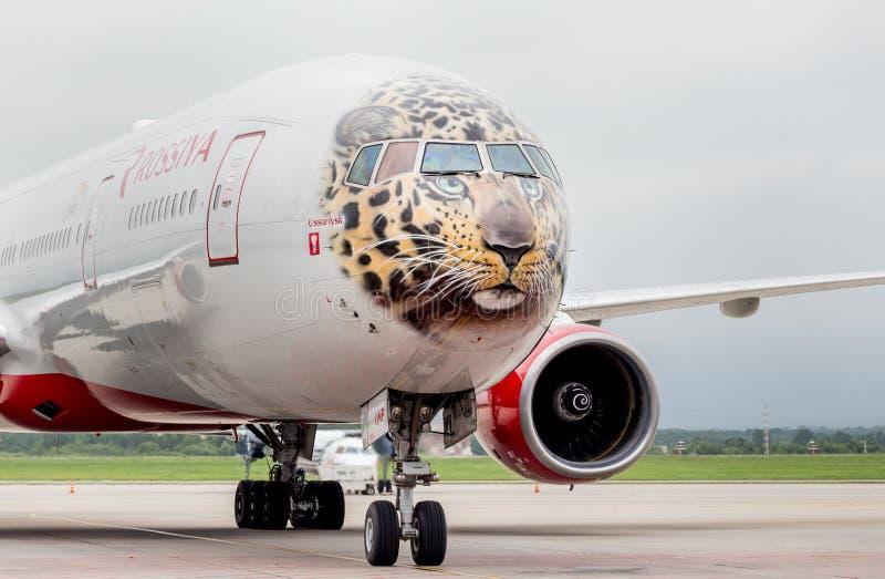 Самолет Боинг 777-300 пассажира авиакомпаний Rossiya на взлетно-посадочной дорожке Фюзеляж покрашен как сторона дальневосточного  стоковые изображения rf