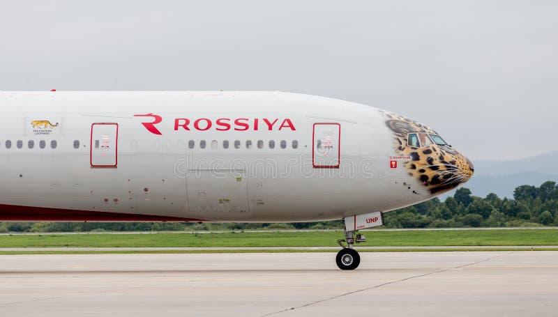Самолет Боинг 777-300 пассажира авиакомпаний Rossiya на взлетно-посадочной дорожке Фюзеляж покрашен как сторона дальневосточного  стоковая фотография