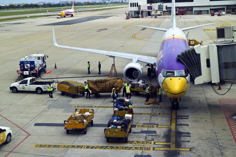Самолет будучи дозаправлянным и нагруженный с багажом в Бангкоке стоковое изображение