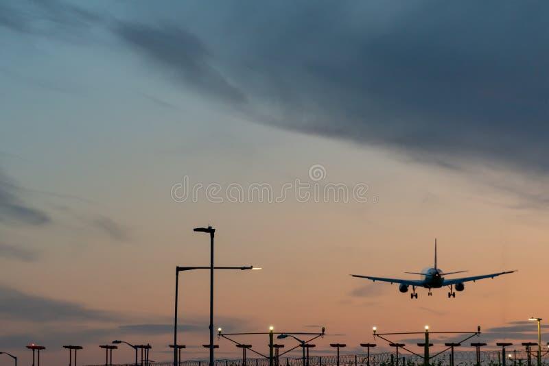 Самолет взлетает с взлетно-посадочной полосы аэропорта на закате стоковые фото