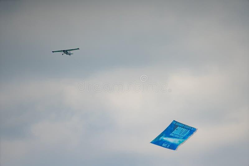 Самолет вытягивая знамя фильма Godzilla в небе стоковое изображение rf
