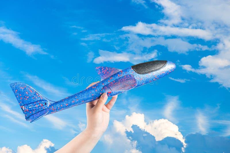 Самолет игрушки в руке на предпосылке голубого неба с облаками Мечты, каникулы или концепция перемещения стоковое фото