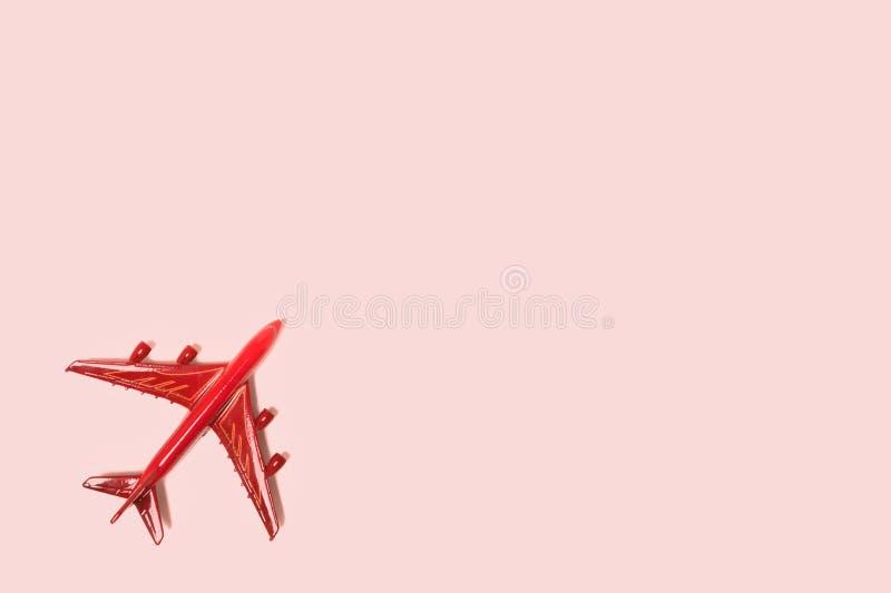 Самолет игрушки красный на розовой предпосылке   стоковое изображение rf
