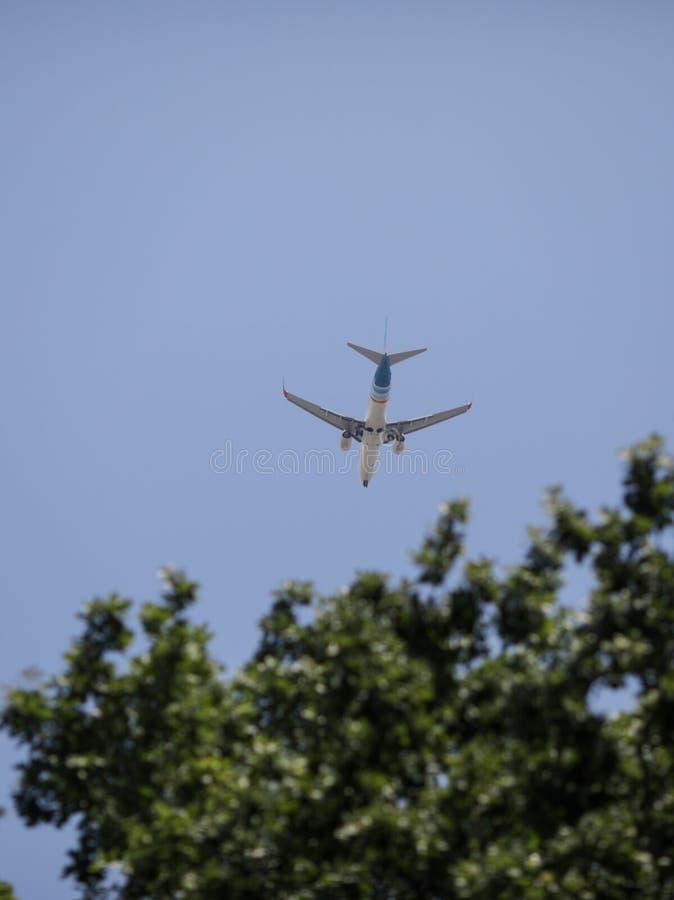 Самолет коммерческой авиакомпании может быть увиденный летать над зелеными деревьями стоковые фотографии rf