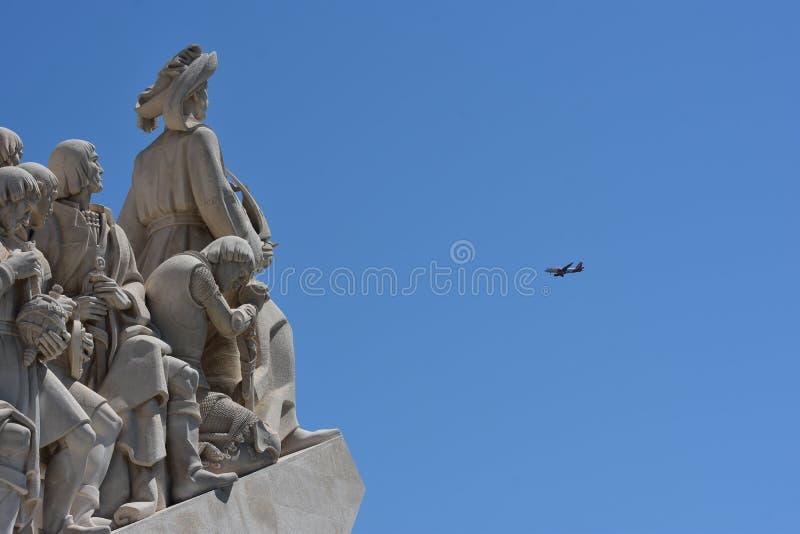 Самолет летает на вид памятника 'Открытия' в Лиссабоне стоковые изображения rf