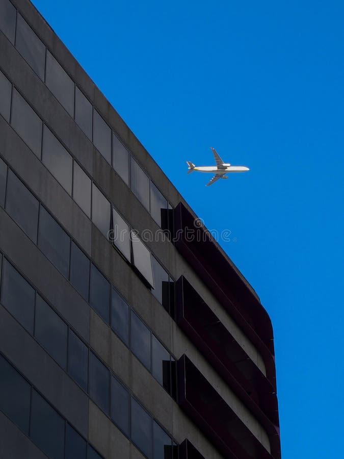 Самолет летая над офисным зданием стоковая фотография