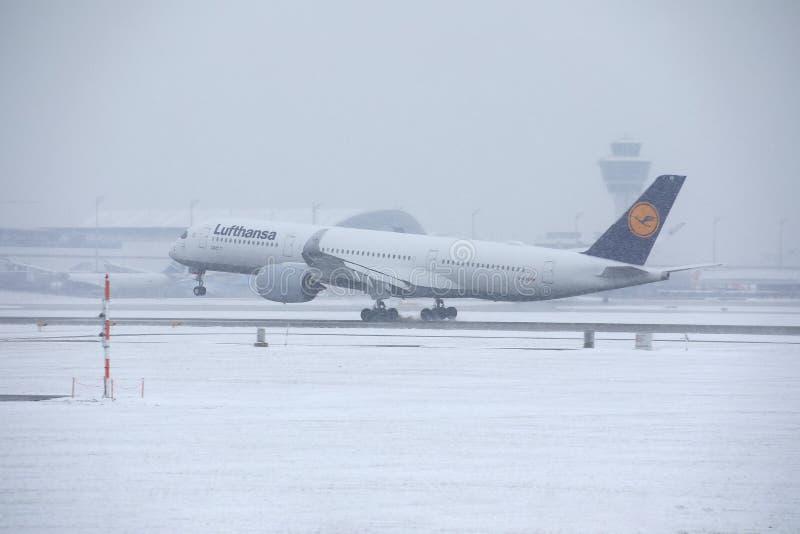 Самолет Люфтганзы принимая от снежного взлётно-посадочная дорожка стоковые фото