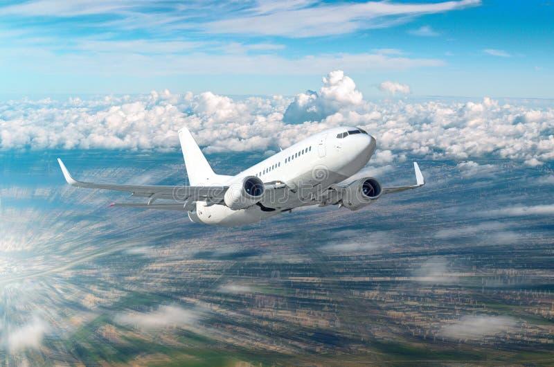 Самолет на быстром ходе высоты подъема летает над городом стоковое фото