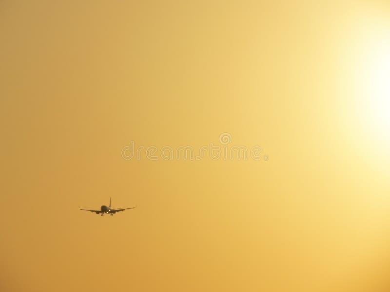 Самолет на желтом ярком небе стоковые фотографии rf