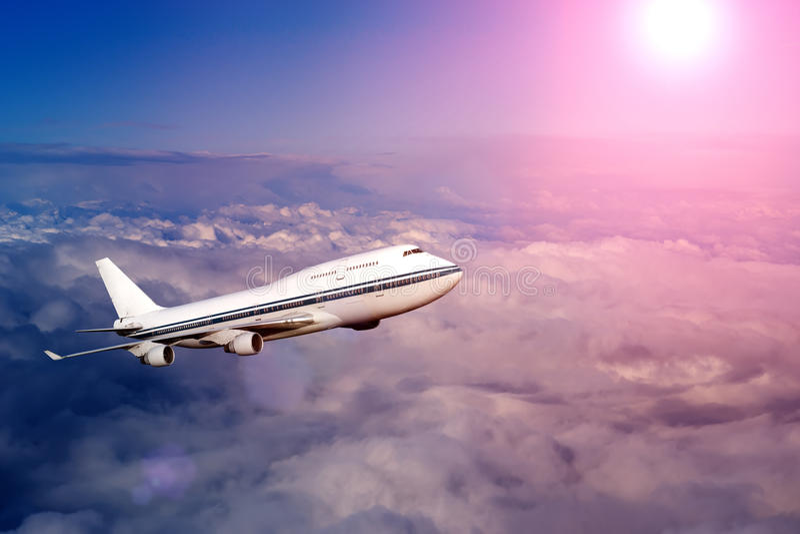 Самолет пассажира в облаках на заходе солнца или рассвете стоковое изображение rf