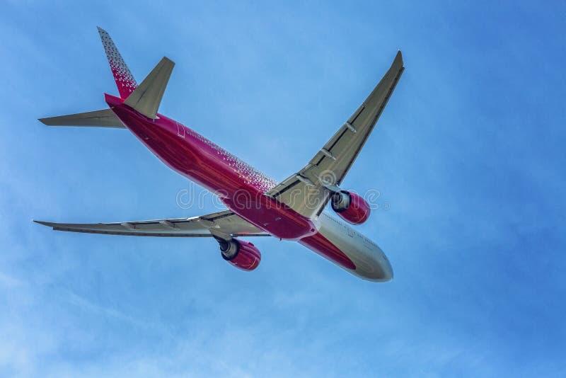 Самолет пассажира в пасмурном ярком голубом небе Чувство свободы Идти прочь стоковое фото