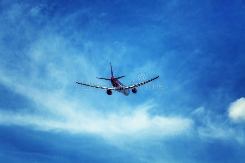 Самолет пассажира в пасмурном ярком голубом небе Чувство свободы Идти прочь стоковое фото rf