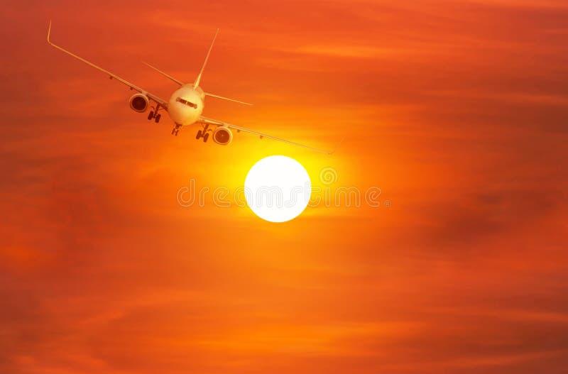 Самолет пассажира летая прочь внутри к высоченной высоте над солнцем во время захода солнца стоковое фото