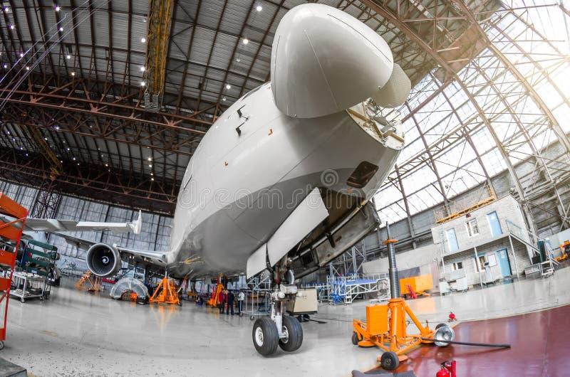 Самолет пассажира на обслуживании двигателя и фюзеляж проверяют ремонт в ангаре авиапорта С открытым клобуком на носе под c стоковая фотография