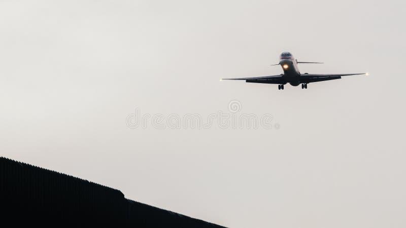 Самолет причаливает взлётно-посадочная дорожка для того чтобы приземлиться на авиапорт стоковая фотография