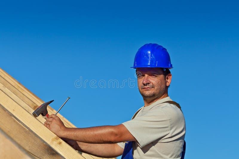 Самолюбивый рабочий-строитель на крыше стоковые изображения