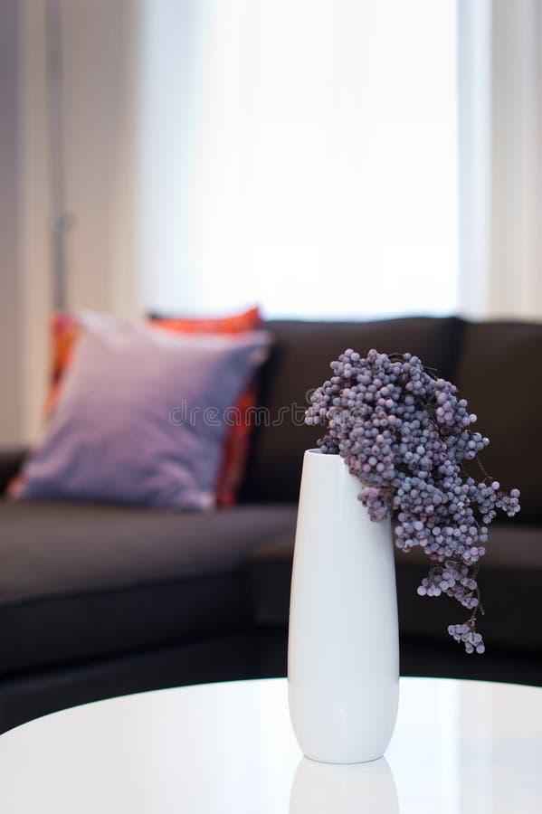Самомоднейшая белая ваза с лиловым цветком в живущей комнате стоковое изображение
