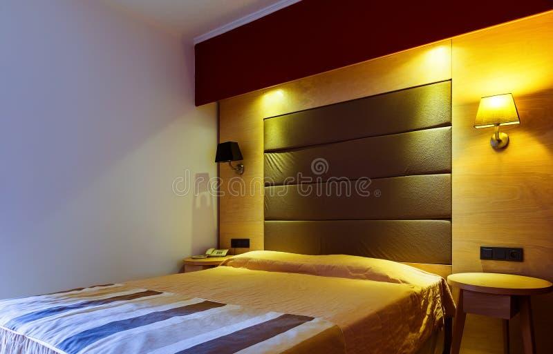 Самомоднейшие, теплые, приглашая спальня или гостиничный номер Свет и тени стоковое фото rf