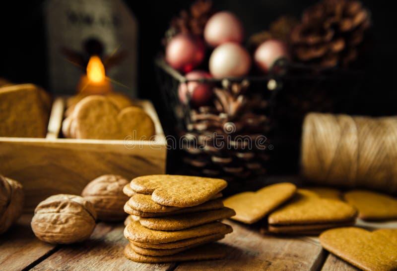 Самонаведите испеченные печенья перца пряника рождества штабелированные, в деревянной коробке Красочные безделушки, конусы сосны  стоковое изображение rf