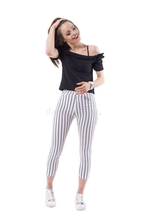 Самопроизвольно усмехаясь ультрамодная молодая женщина смотря вниз с регулировать волосы с рукой стоковая фотография